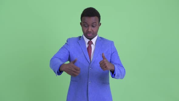 Thumbnail for Confused Young African Businessman Choosing Between Thumbs Up and Giving Thumbs Down