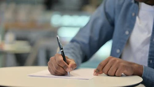 African Man Writing on Paper Close Up
