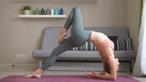 Pretty Girl Is Focused on Yoga Practice at Home Doing Balancing Exercises