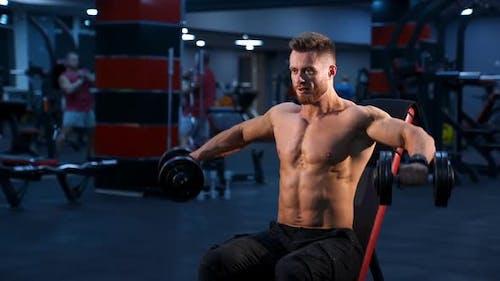 Hübscher Power athletischer Mann Bodybuilder macht Übungen mit Hanteln.