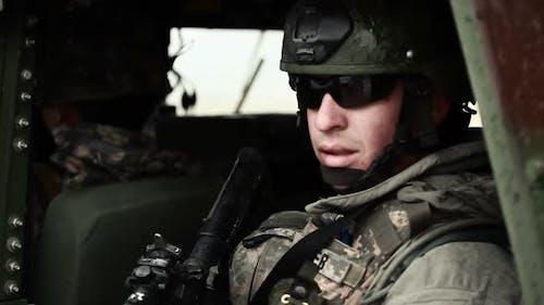 Soldier wearing sunglasses looking out side door of Humvee