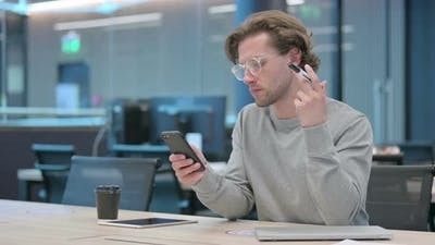 Young Businessman with Pen Using Smartphone in Office