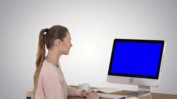 Thumbnail for Girl Sitting in Front of the Computer Monitor and Watching Something Smiling Blue Screen Mock-up