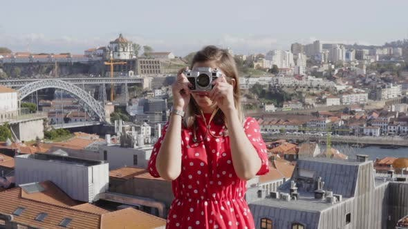 Thumbnail for Woman in Red Dress Is Taking a Photo on Vintage Camera