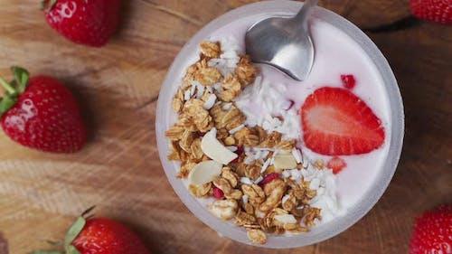 Scooping Yogurt with Muesli and Strawberries
