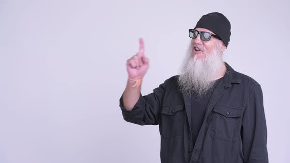 Thumbnail for Happy Mature Bearded Hipster Man Thinking While Pointing Up