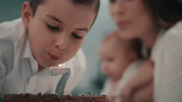 Thumbnail for Boy Blowing Candle on Birthday Cake at Family Party