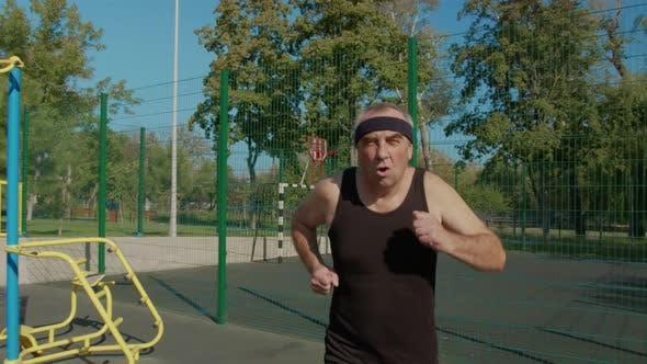 Elderly Man Doing Exercise. Senior Man Running in Park. Health Lifestyle and Exercise Concept.