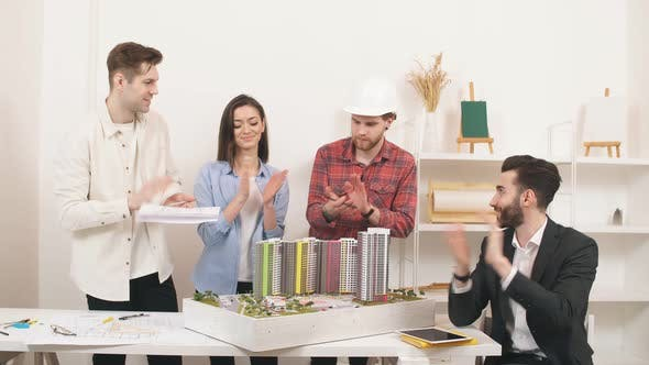 Four Architects Standing Around Table Having Meeting
