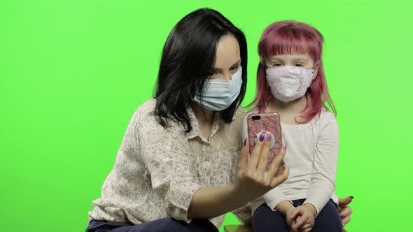 Thumbnail for Mother, Daughter Wearing Medical Mask Holding Smart Phone Talking on Video Call