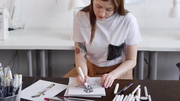 Fashion Designer Drawing Female Dress at Desk in Sewing Studio