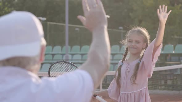 Thumbnail for Cute Little Smiling Happy Girl with a Tennis Racket in Her Hands Standing on the Tennis Court