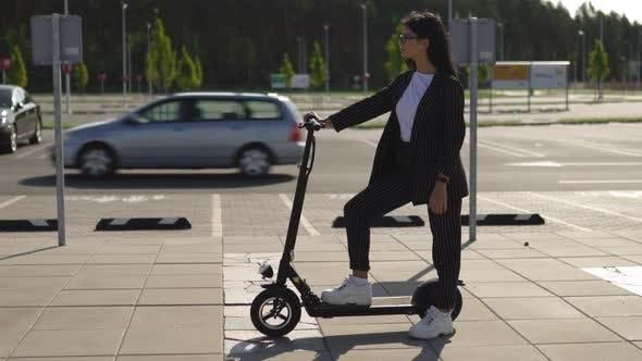 Epische Geschäftsfrau steht mit Elektroroller auf Parkplatz