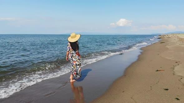 Thumbnail for Brunette Girl in Hat Walking at Seaside