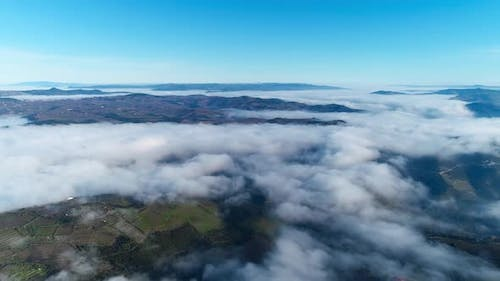 Aerial Drone View Above the Clouds and Covered Mountains in the Winter