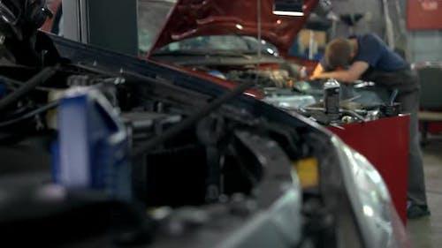 Professional Mechanic Repairing Car in a Service Center