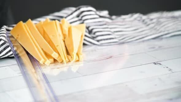 Thumbnail for Schritt für Schritt. Einen Gourmet-Käse auf einem weißen Schneidebrett mit einem Küchenmesser schneiden.