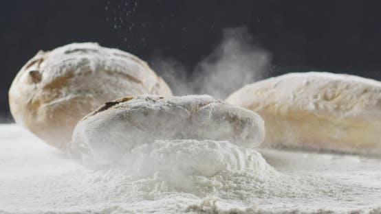 Thumbnail for Bäckerei- und Kochkonzept Frisches Brot mit Splash fällt in Mehl