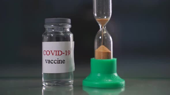 Vials of Coronavirus Vaccine and an Hourglass in the Foreground