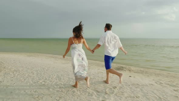 Thumbnail for Young Man and Woman Hold Hands, Run Barefoot Along the Beach Happy Holidays and Honeymoon