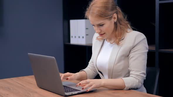 Confident Middle-Aged Woman Is Working on Laptop at Table in Concentration