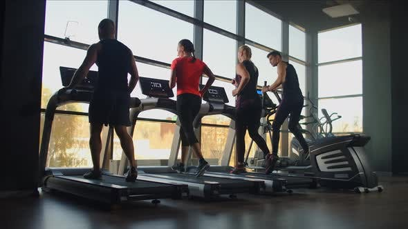 Thumbnail for Fitness Couple Running on Treadmill Machine in Gym Club Together. Handsome Man Training Woman on Run