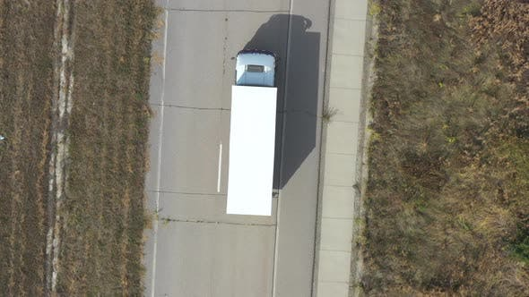 Thumbnail for Aerial View of Truck with Trailer Driving on Straight Road and Transporting Goods. Flying Over
