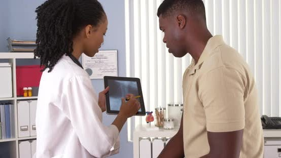 Thumbnail for Female African American doctor explaining x-ray to patient on tablet