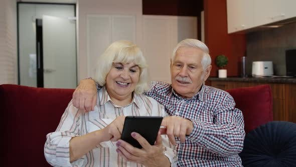 Thumbnail for Senior Old Couple Grandparents Talking and Using Digital Tablet Computer at Home. Internet Shopping