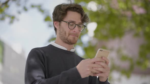 Thumbnail for Smiling Man in Eyeglasses Using Smartphone