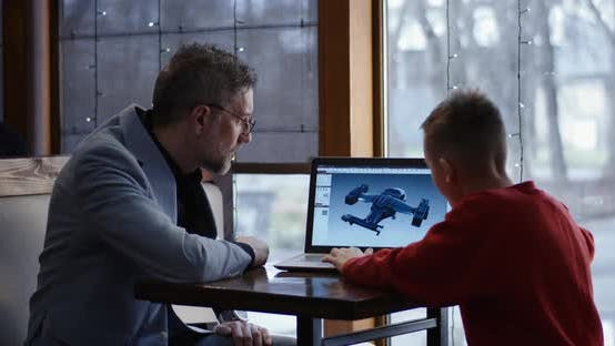 Businessman and Young Graphic Designer Discussing 3D Model