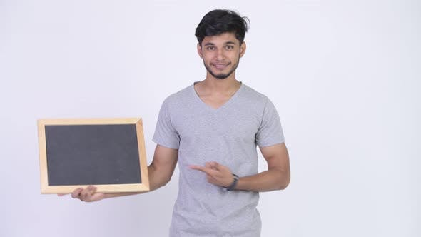 Cover Image for Young Happy Bearded Indian Man Showing Blackboard and Giving Thumbs Up