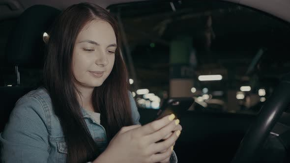 Thumbnail for Woman Uses an Application on His Phone While Sitting in the Car in the Parking Lot