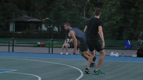 Geschickter Basketballspieler in Uniform, dribbelt den Ball, übergibt den Verteidiger des Gegners und