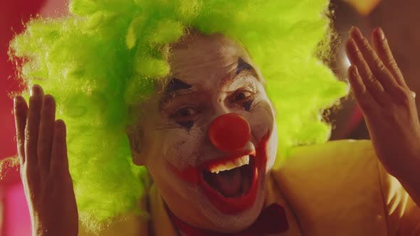 Thumbnail for A Crazy Smiling Clown Closing His Face with His Hands and Performing Creepy Emotions