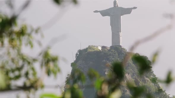 Christ statue atop Corcovado seen through tree foliage
