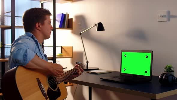 Thumbnail for Young Man with Laptop Playing Guitar at Home