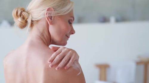Back View of Mid Age Woman Applying Body Cream