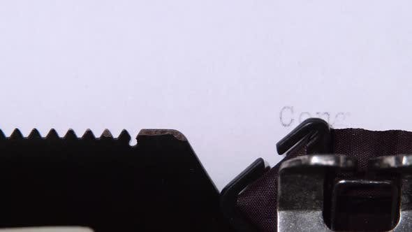 Thumbnail for Head Writes the Word Congratulations on a Sheet of a Typewriter. Close Up