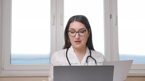 Female Doctor with Glasses and Stethoscope Consults the Patient at Online with Laptop