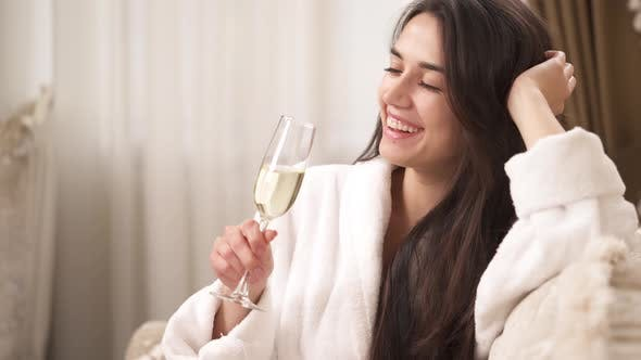 Cover Image for A Side View of a Pretty Brunette Sitting Inside and Holding a Half-full Wine Glass