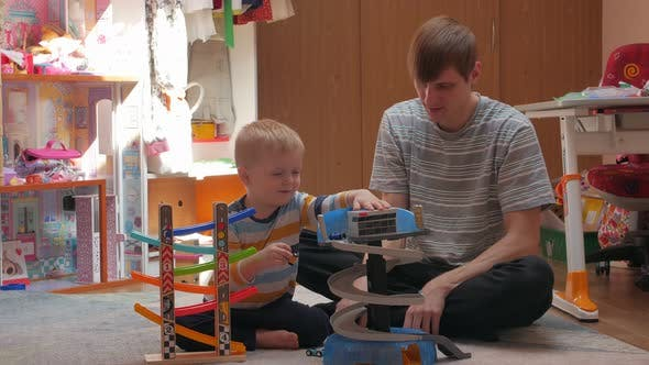 Man And Boy Playing Cars