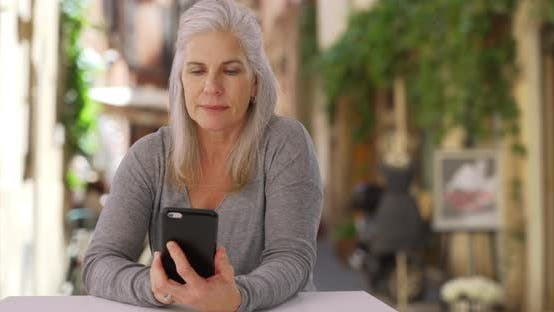 Thumbnail for Casual mature Caucasian female uses smartphone while relaxing at café in Europe