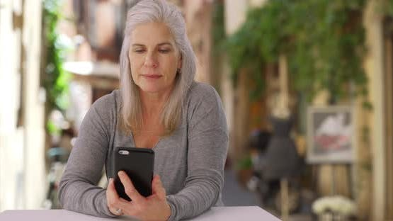 Casual mature Caucasian female uses smartphone while relaxing at café in Europe