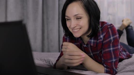 Thumbnail for Junge Frau liegend auf Bett und mit Video Chat mit Webcam auf Laptop Computer