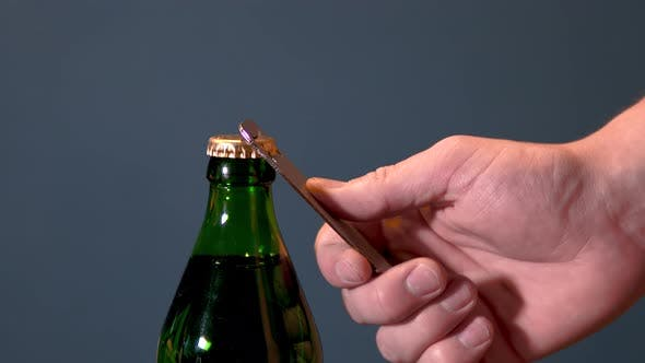 Thumbnail for Man Opens Bottle with Fizzy Drink with a Special Opener. Glass Bottle with Metal Lid