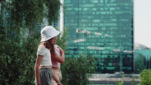 Two Young Girls Walking in Urban Cityscape