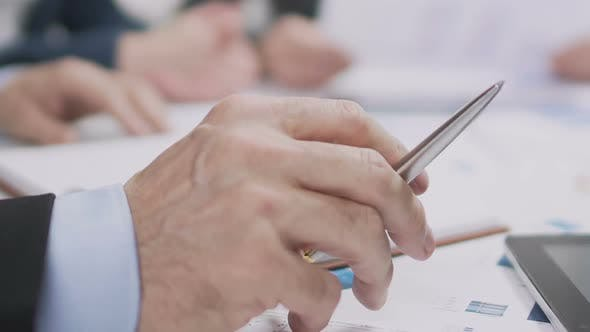 Thumbnail for Male Hand Holding Pen At Business Meeting, Planning Profitable Year For Company