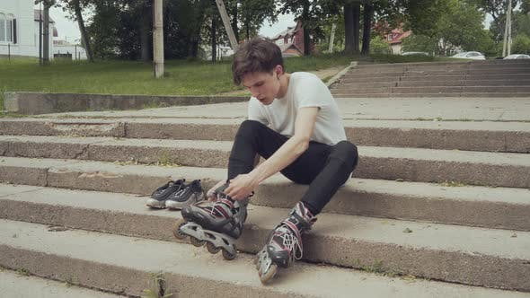 Young Man Puts on Roller Skates
