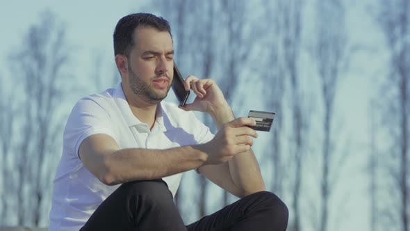 Cover Image for Concentrated Young Man Dictating Card Number Through Phone